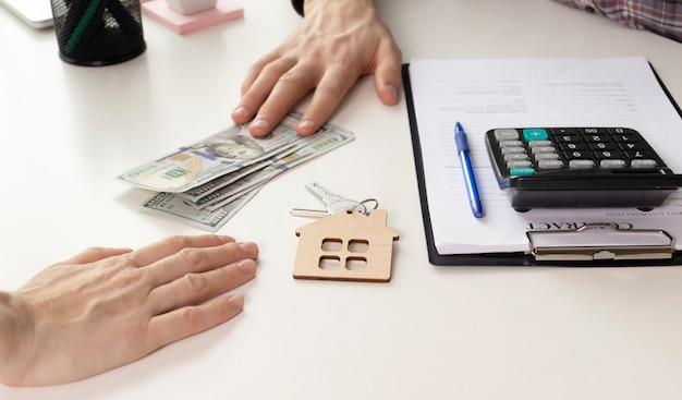 不動産の譲渡権のために不動産の購入または賃貸を終えた後、住宅開発業者と顧客が握手を交わす