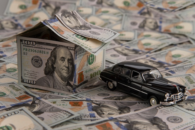 A house of dollar bills and a car on scattered bills