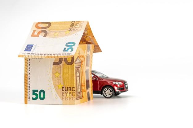 白で隔離されるユーロ紙幣と車からの家。ローン、不動産、自動車保険のコンセプト