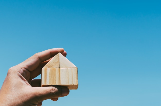 House from wooden block in human hand with blue sky