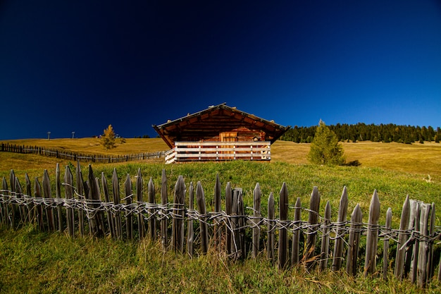 House in a grassy field with a wooden fence in dolomite italy