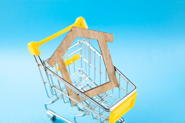 Дом в корзине. концепция покупки дома на синей сцене