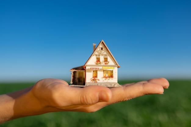 Дом в руке против весеннего зеленого поля и поверхности голубого неба