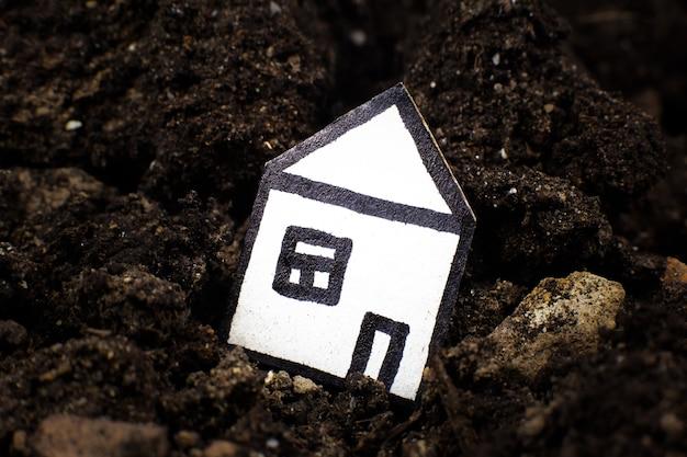 土の家、地球の割れ目に落ちる。地震と家の喪失の概念。債務を信用する。