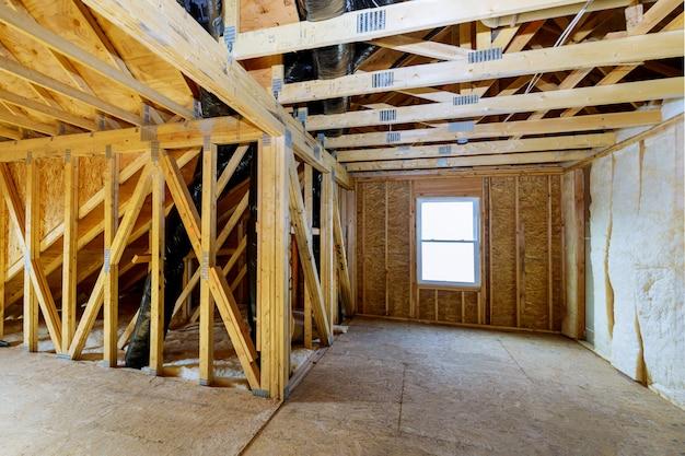 断熱材で建設中の未完成の家の屋根裏部屋の壁屋根