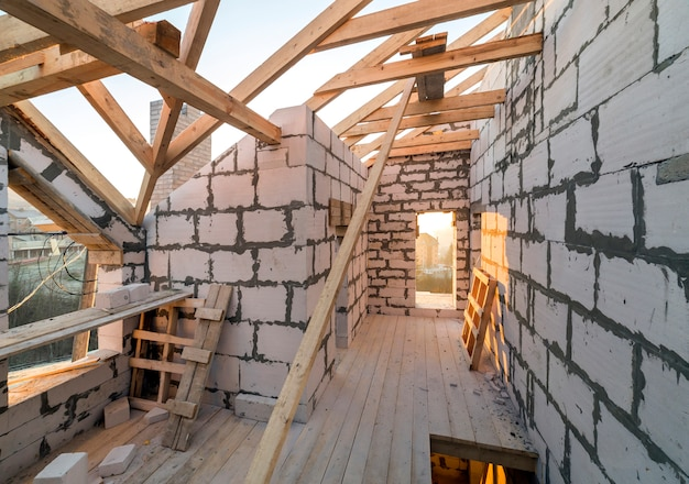 House interior under construction and renovation. energy saving walls of hollow foam insulation blocks and bricks, ceiling beams and roof frame.