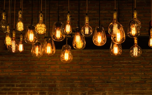 House interior of loft and rustic style. beautiful vintage luxury light bulb hanging decor glowing in dark. retro filter effect style. blend of history and modern.