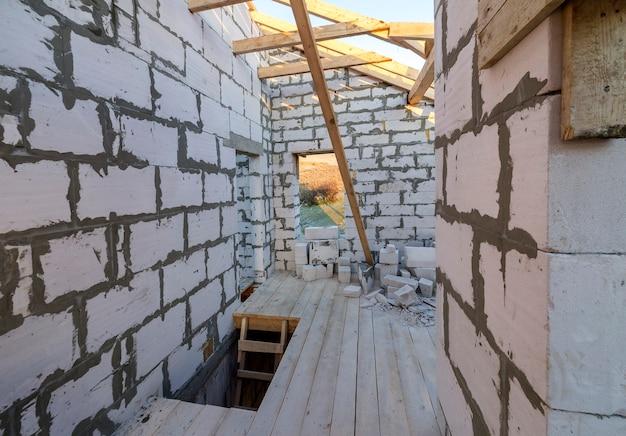 建設中の家のインテリア。中空発泡断熱ブロックとレンガの天井壁、天井梁と屋根フレーム。