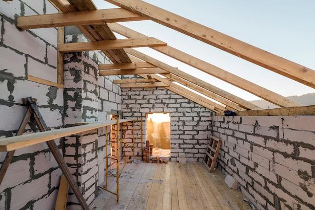 건설 및 개조중인 주택 내부입니다. 중공 폼 단열 블록 및 벽돌, 천장 빔 및 지붕 프레임의 에너지 절약 벽.