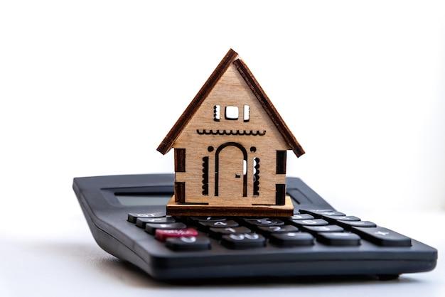 Дом стоит на калькуляторе. планирование сбережений на покупку дома для приобретения недвижимости, ипотеки и инвестиций в недвижимость.
