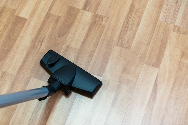 House keeper using vacuum machine to clean a wooden floor.