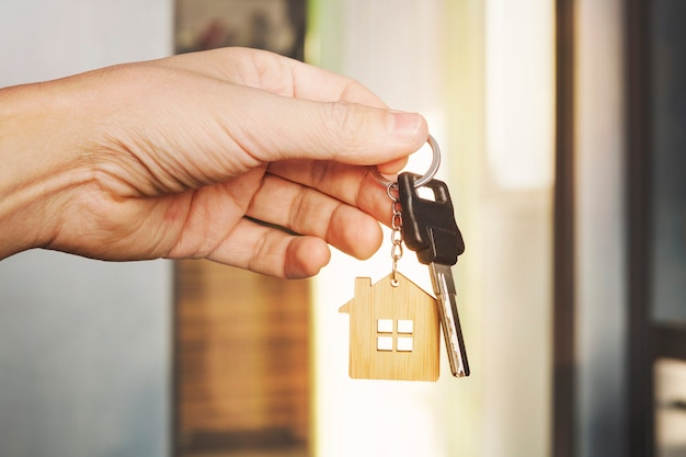 House key in male hand at apartment background. house key ring. concept of moving in new living apartment. symbol of purchasing house. estate investment. buy property. real estate transaction.