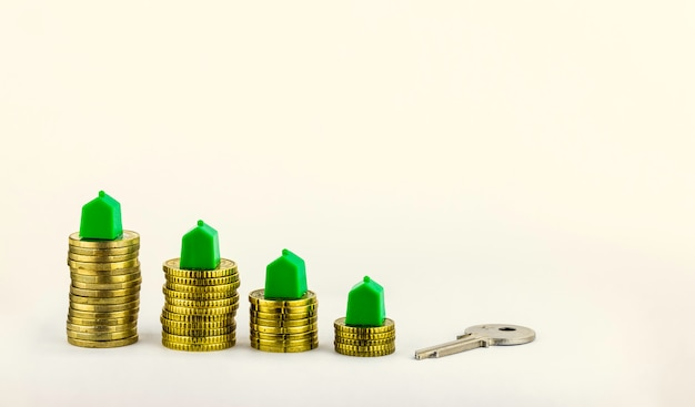 House key and mini houses about the coins, real estate investment, save money with stack coins