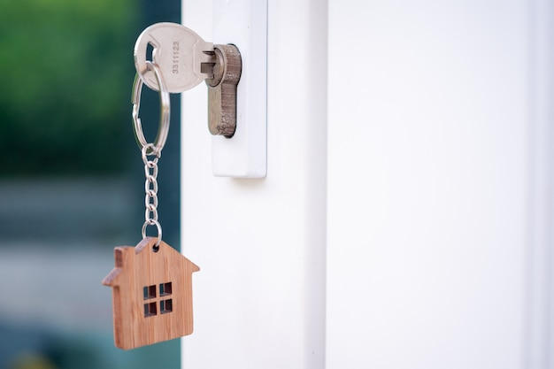 A house key with a key ring inserted at the door lock. buy new home concept.