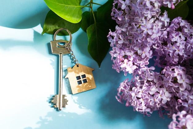 푸른 봄 배경과 라일락 나뭇가지에 열쇠고리가 달린 집 열쇠. 여름 휴가용 주택, 시골에 있는 별장 예약, 새 집으로 이사, 모기지, 부동산 임대 및 구매. 관광 여행