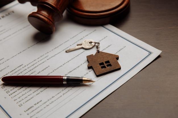 家の鍵と家の販売の署名された契約のお金。キーに焦点を当てます。