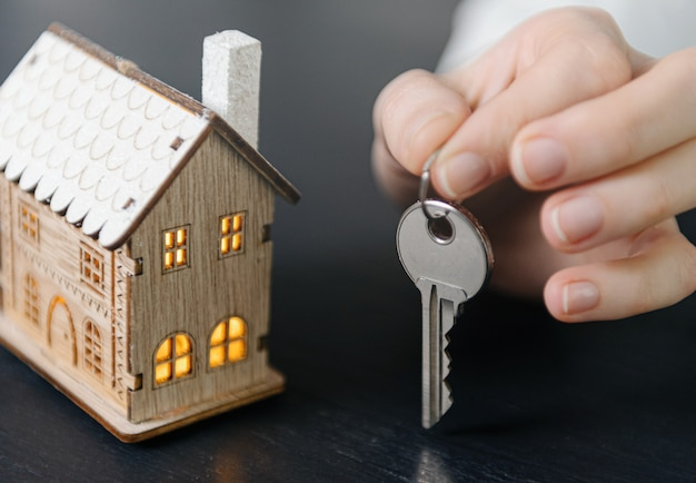 House keys in the hands of a woman and a small model of a house with luminous windows nearby. concept of acquiring your home