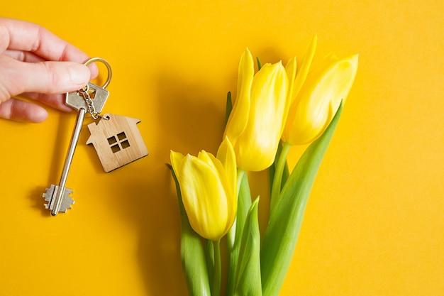 黄色の背景と春のチューリップに手に家の鍵。