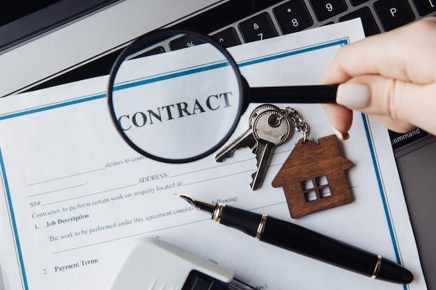 家の鍵、虫眼鏡、契約書。家賃、検索または住宅ローンの概念。