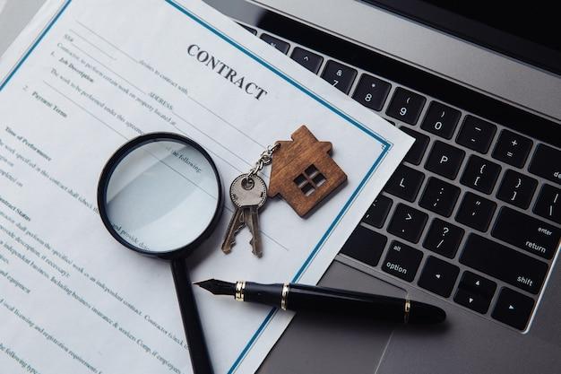 Ключи от дома, увеличительное стекло и контракт на ноутбуке. понятие аренды, поиска, покупки недвижимости. вид сверху.