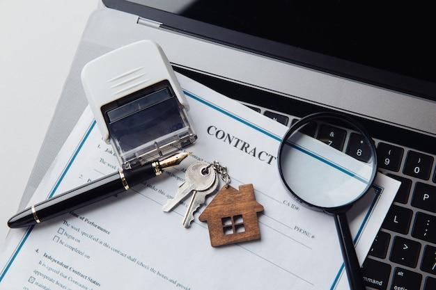 Ключи от дома, увеличительное стекло и контракт