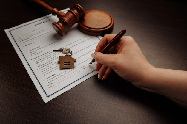House keys and money on a signed contract of house sale. focus on keys.