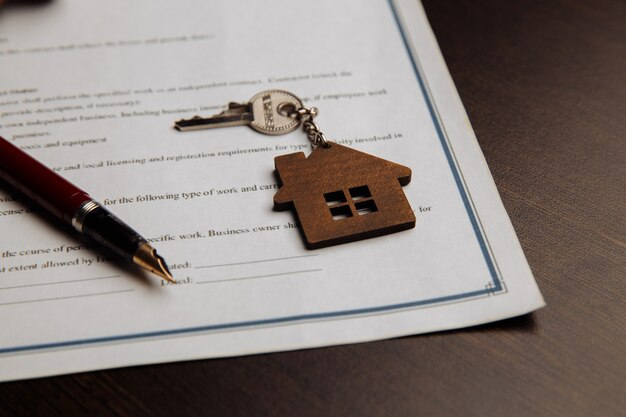 House keys and money on a signed contract of house sale.