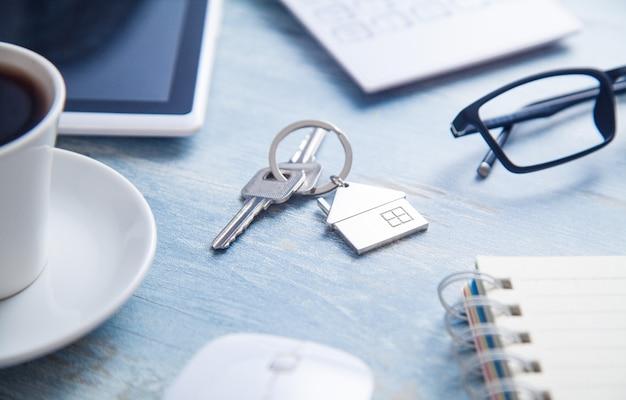 Ключи от дома на столе с бизнес-объектами.