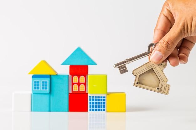 집 모양의 열쇠 고리와 목조 미니 모델 하우스가있는 집 열쇠