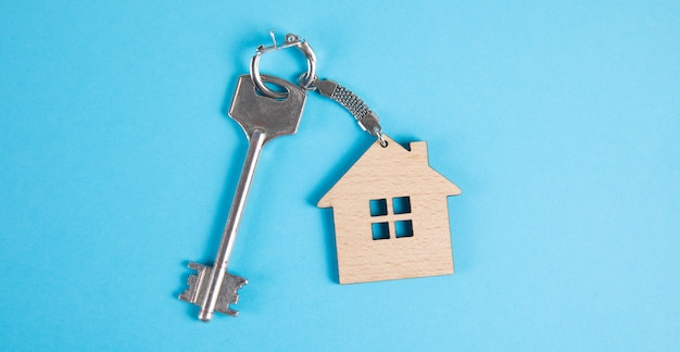 House keys with keychain on blue surface