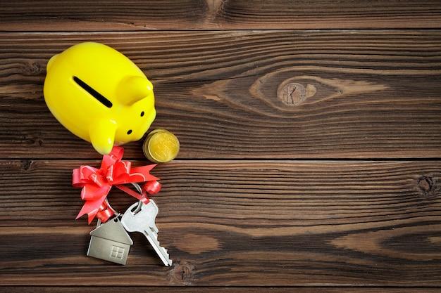 木製のテーブルにリボンの弓と貯金箱が付いている家の鍵