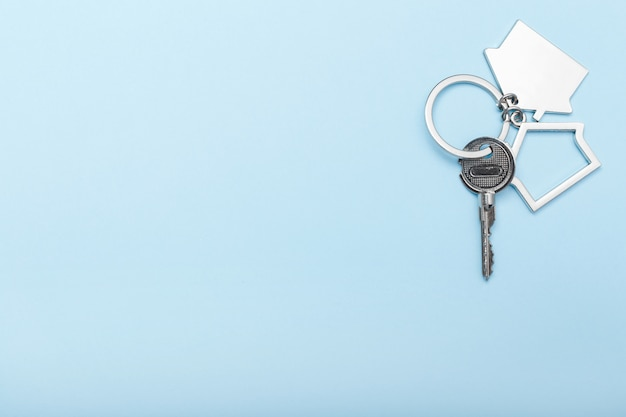 House keys with trinket on color background, top view with copy space. house key on blue background. minimal flat lay style with place for text.
