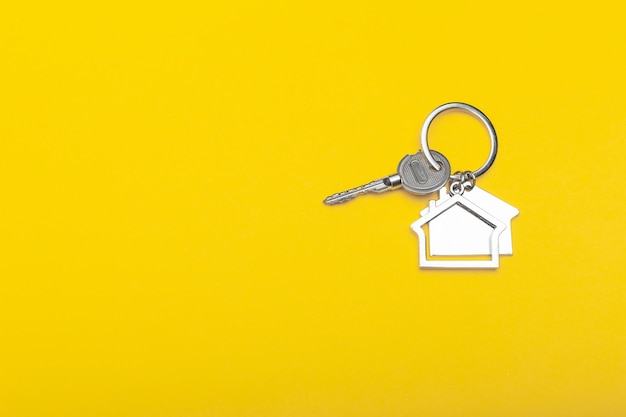 House keys with trinket on color background, top view with copy space. house key on yellow background. minimal flat lay style with place for text.