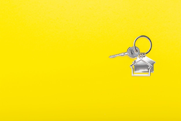 House keys with trinket on color yellow background