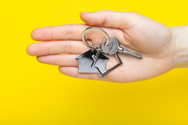 House keys with trinket in female hand on color background, top view with copy space. house key on yellow background. minimal flat lay style with place for text.