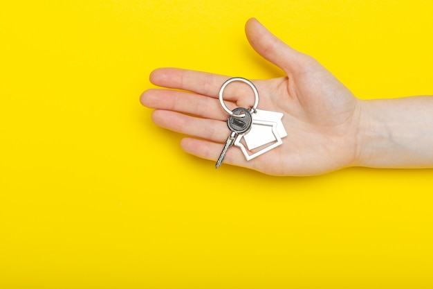 House keys with trinket in female hand on color, top view with copy space.