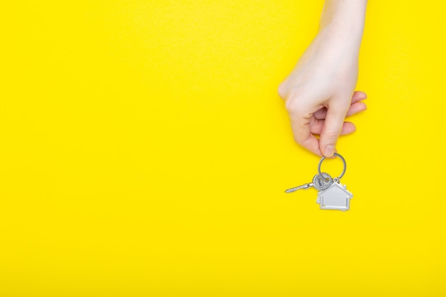 Расквартируйте ключи с побрякушкой в женской руке на предпосылке цвета, взгляд сверху с космосом экземпляра. ключ от дома на желтом фоне. минимальный стиль плоской планировки с местом для текста.