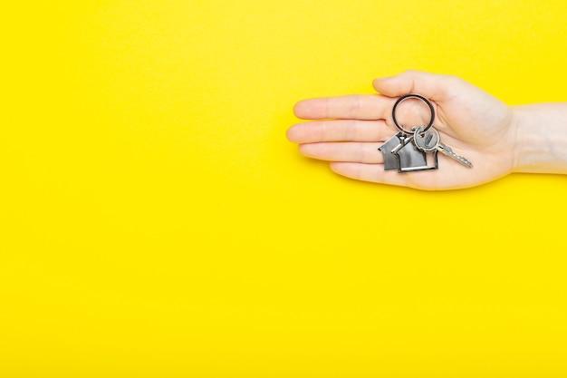 Ключи от дома с безделушкой в женской руке на цветном фоне, вид сверху с копией пространства.