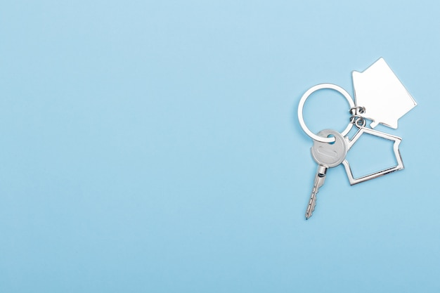 House keys with trinket keychain house symbol on color blue background