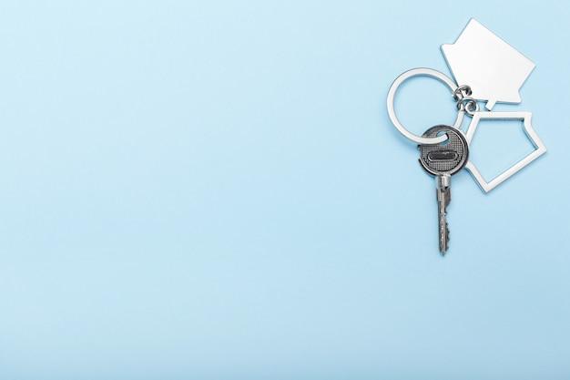 Расквартируйте ключи с побрякушкой на предпосылке цвета, взгляд сверху с космосом экземпляра. ключ от дома на синем фоне. минимальный стиль плоской планировки с местом для текста.