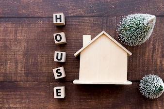 House letter blocks near the estate model with two christmas tree on wooden textured backdrop