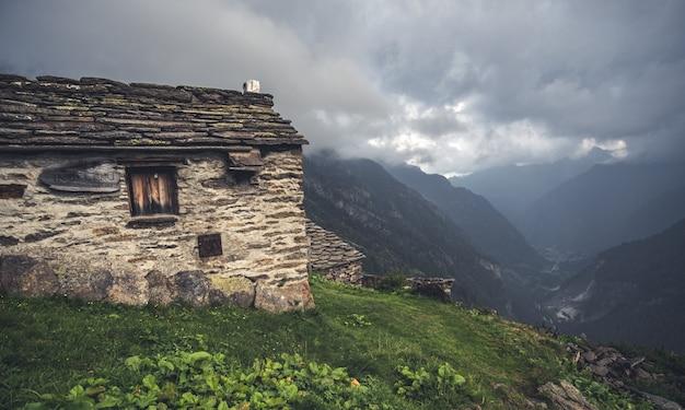 パノラマの高山の谷を見下ろす家