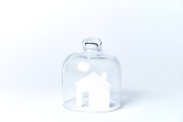 A house made of white paper under glass