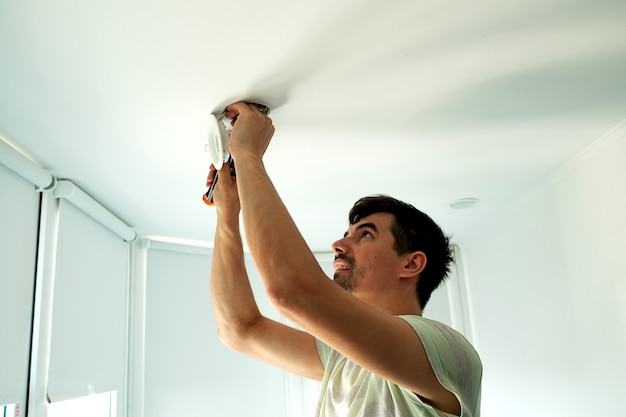 하우스 마스터 남성 전기 기술자는 흰색 방에 있는 실내 천장 조명을 수리합니다.