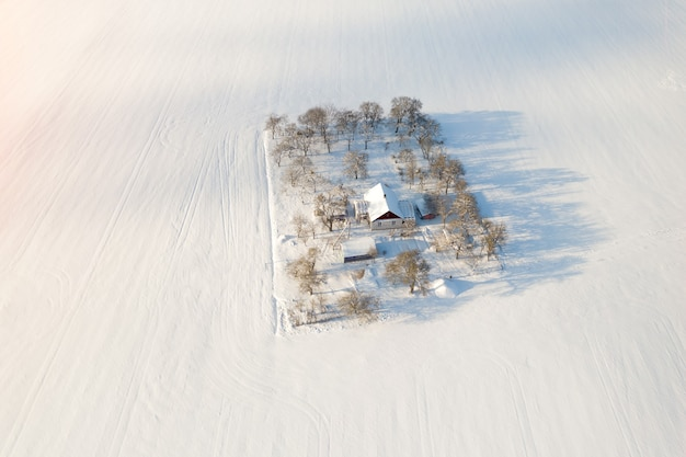 House in the middle of a snow field top view.