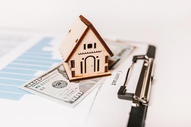 Миниатюрная модель дома и деньги по документам. инвестиции, недвижимость, дом, жилье