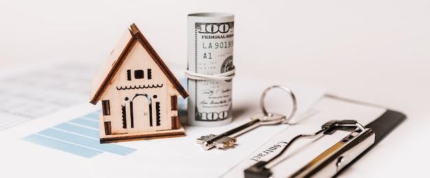 家のミニチュアモデルとドキュメントのお金。