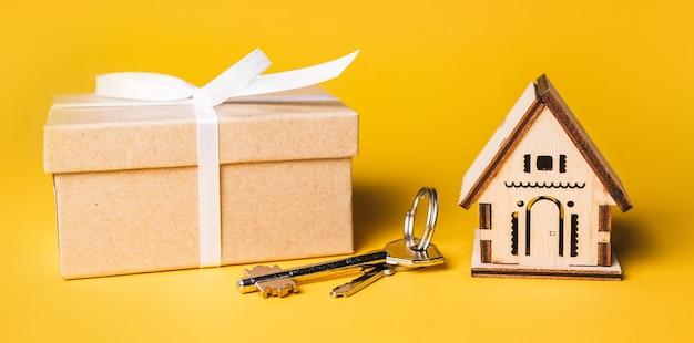 家のミニチュアモデル、ギフト、鍵。投資、不動産、住宅、住宅