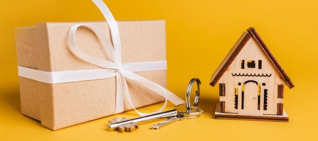 黄色の背景に家のミニチュアモデル、ギフト、鍵。投資、不動産、住宅、住宅