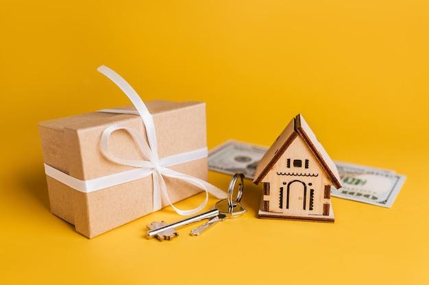 黄色の背景に家のミニチュアモデル、ギフト、鍵、お金。投資、不動産、住宅、住宅